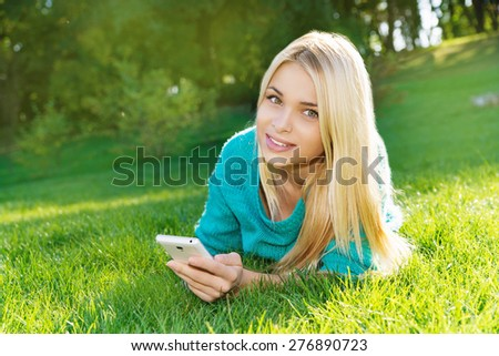 Beautiful Young Woman Lying on Green Grass outdoor. Park. Meadow. Summer. Holding in her hand mobile telephone. Youth concept - stock photo