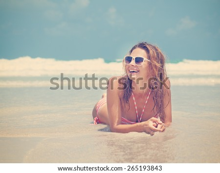 beautiful young woman lying on the beach against the sea, image with retro toning - stock photo