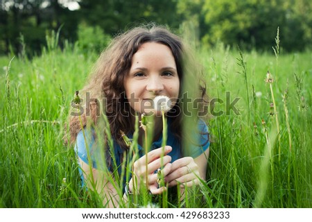 Beautiful young woman lying on the grass smiling - stock photo