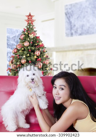 Beautiful young woman lying on the sofa while holding her dog and smiling at the camera, shot with a christmas tree background on the back - stock photo