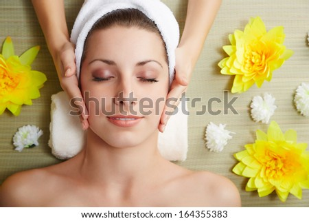 Beautiful young woman lying relaxed in a spa salon and receiving facial massage. Beauty treatment. - stock photo