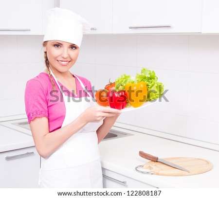 beautiful young  woman making salad in the kitchen at home - stock photo