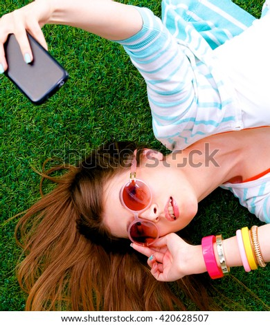 Beautiful young woman making selfie by her phone while lying in green grass - stock photo