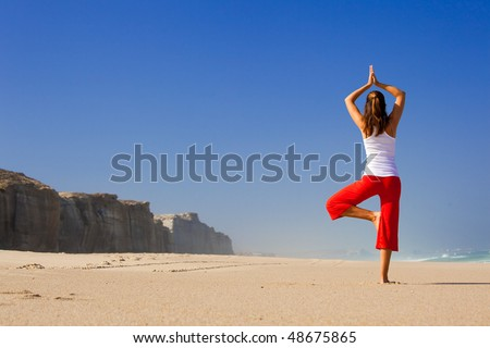 Beautiful young woman making Yoga exercises on the beach - stock photo