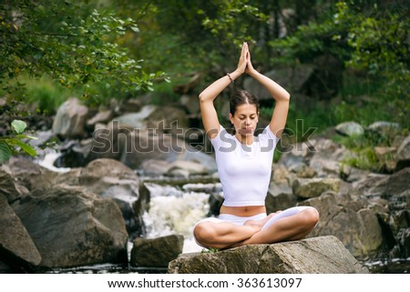 Beautiful young woman meditating in yoga pose at a mountain stream. - stock photo