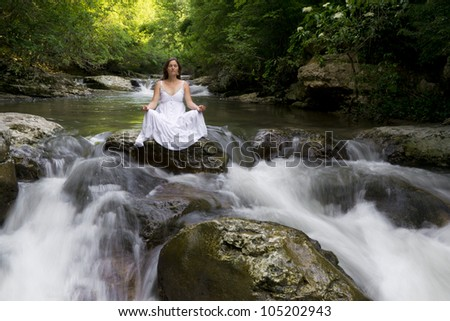 Beautiful young woman meditating surrounded by the purifying waters of a clear mountain stream - stock photo