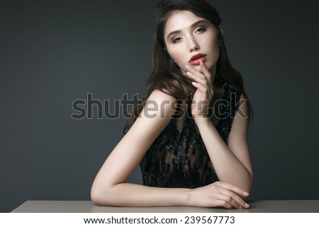 Beautiful young woman model with red lips, manicure, evening makeup posing in black dress on dark background - stock photo