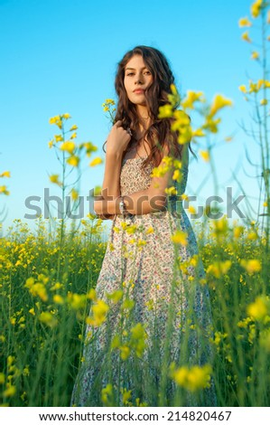 beautiful young woman moving and posing in the rapeseed field - stock photo