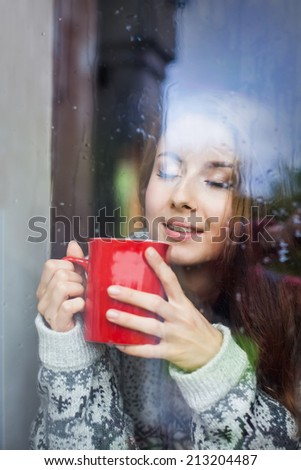Beautiful young woman on a balcony enjoying morning with cup of coffee - stock photo