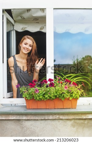 Beautiful young woman on a balcony greeting someone - stock photo