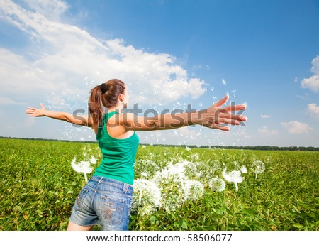 Beautiful young woman on a green meadow - stock photo