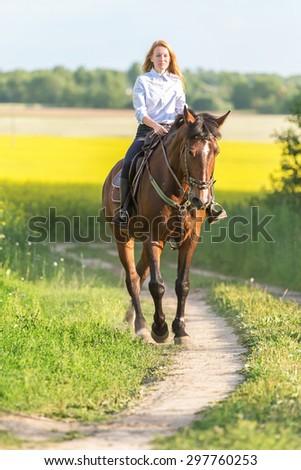 Beautiful young woman on horseback. - stock photo