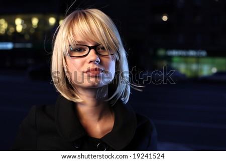 Beautiful young woman on night street, close-up. - stock photo