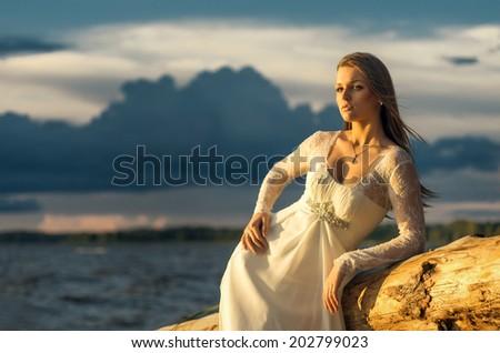 beautiful young woman on sunset beach - stock photo