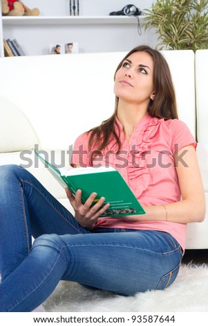 beautiful young woman on the couch with a book - stock photo
