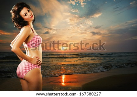 Beautiful young woman on the sea beach at sunset - stock photo