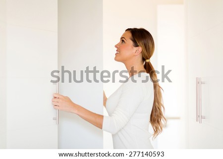 beautiful young woman opening wardrobe doors - stock photo