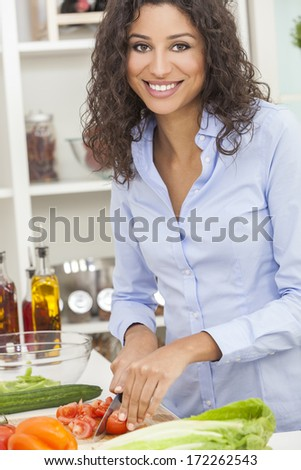 Beautiful young woman or girl preparing slicing healthy salad fresh food vegetables in kitchen at home - stock photo