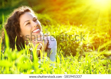 Beautiful Young Woman Outdoors. Enjoy Nature. Healthy Smiling Girl in Green Grass. - stock photo