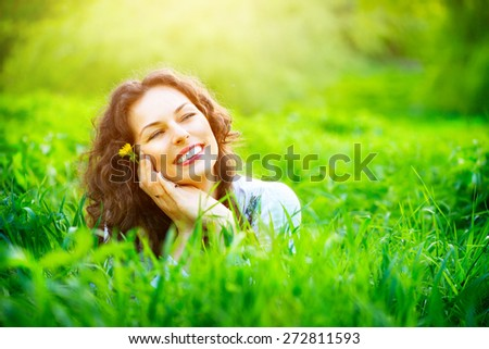 Beautiful Young Woman Outdoors. Enjoy Nature. Healthy Smiling Girl lying in Green Grass - stock photo