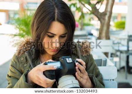 Beautiful young woman outdoors looking at pictures on a camera display. - stock photo