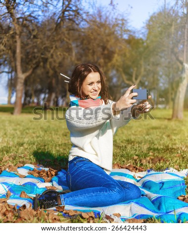 Beautiful Young woman outdoors portrait. Outdoor portrait of pretty student girl taking a selfie. Concept of healthy lifestyle and relaxation. Filtered image. - stock photo