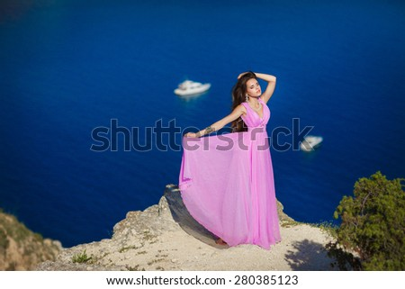 Beautiful young woman outdoors portrait, vogue bride romantic girl on rocks at sea, gorgeous female summer, elegant lady at sea on nature, beauty brunette at sunset enjoying the sun, series - stock photo