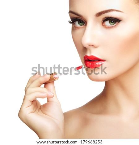 Beautiful young woman paints lips with lipstick. Perfect make-up. Beauty fashion - stock photo