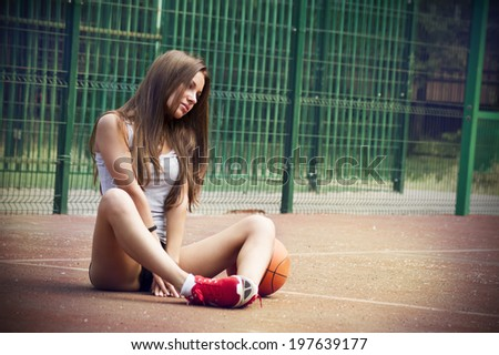 Beautiful young woman playing basketball outdoors.  The girl on the sports ground - stock photo