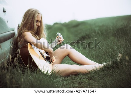 Beautiful young woman playing guitar. Portrait of young adult caucasian cute girl plays acoustic guitar. - stock photo