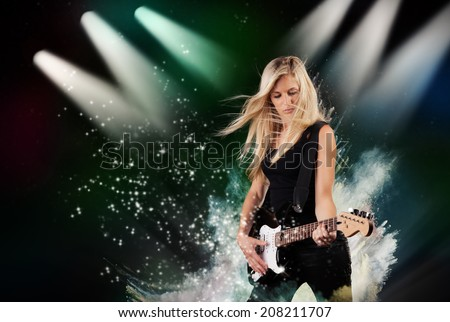 Beautiful young woman playing on electric guitar in water splashes, isolated on black background - stock photo