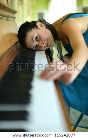 beautiful young woman playing the piano - stock photo
