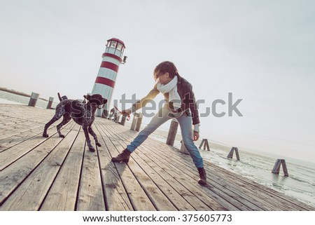 beautiful young woman playing with dog on the sea shore - stock photo