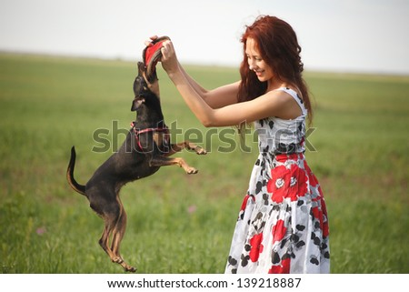 Beautiful young woman playing with her dog in park - stock photo