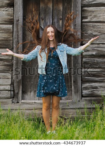 Beautiful young woman playing with her hair in front of old wooden door in short dress - stock photo