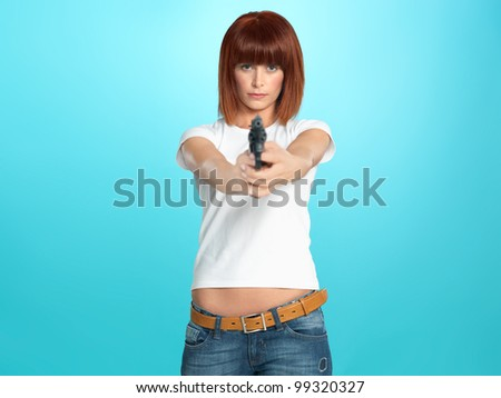 beautiful, young woman pointing a gun at the camera, on blue background - stock photo