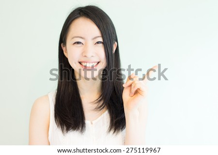 beautiful young woman pointing copy space against light green background - stock photo