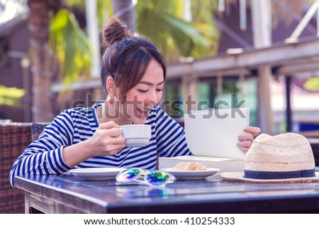 Beautiful young woman portrait reading a book in Outdoor coffee shop - stock photo