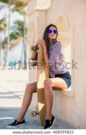 Beautiful young woman portrait with long board on Hollywood beach in Miami, florida. Filtered image. - stock photo