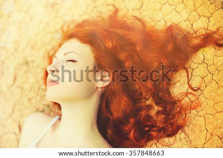 Beautiful young woman portrait with long curly red hair lying on the dried up ground. - stock photo