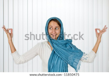 Beautiful young woman posed with a blue scarf and a fun expression. - stock photo