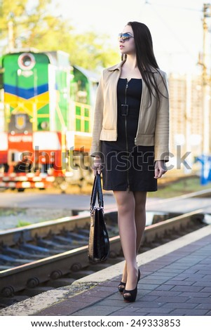 Beautiful young woman posing at the railway station - stock photo