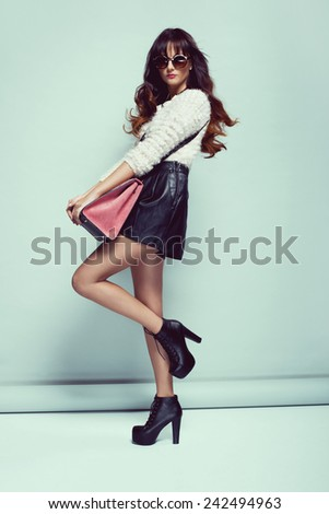 beautiful young woman posing in sunglasses, leather shorts, handbag and sweater - stock photo
