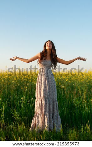 beautiful young woman posing in the rapeseed field - stock photo