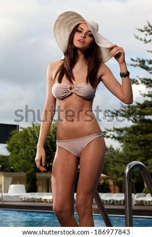 Beautiful young woman posing in the swimming pool .Fashion Colors.  - stock photo