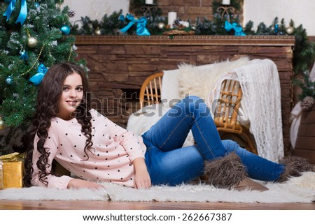 Beautiful young woman posing near the christmas tree and fireplace - stock photo