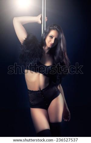 beautiful young woman posing next to pole - stock photo