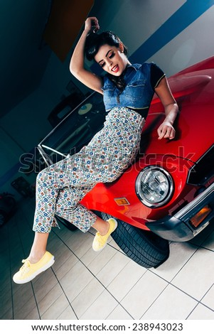 Beautiful young woman posing on a red vintage car - stock photo