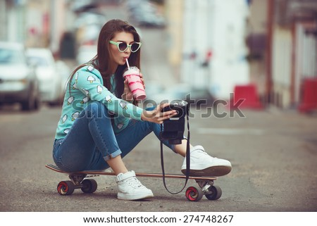 Beautiful young woman posing with a skateboard seat on skate, street fashion lifestyle. Keep cocktail and make selfie photo - stock photo