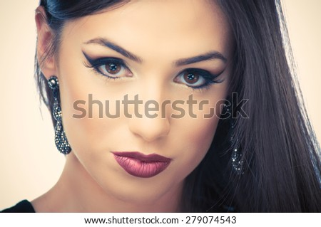 Beautiful young woman posing with earrings - stock photo